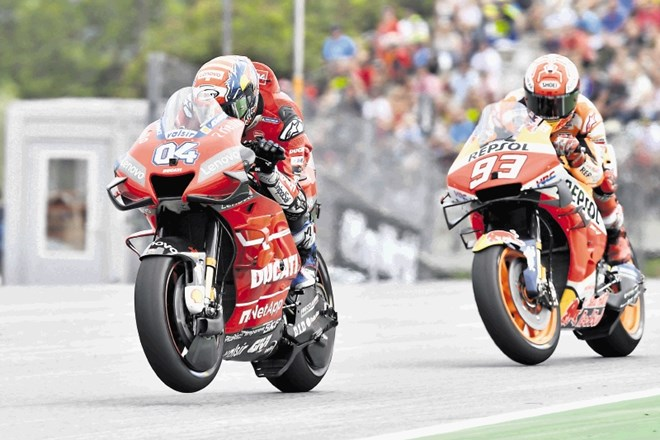 Italian rider Andrea Dovizioso of the Ducati Team steers his motorcycle followed by Spain's rider Marc Marquez of the Repsol...