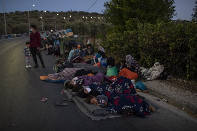 Migrants sleep on the road near the Moria refugee camp on the northeastern island of Lesbos, Greece, Thursday, Sept. 10,...