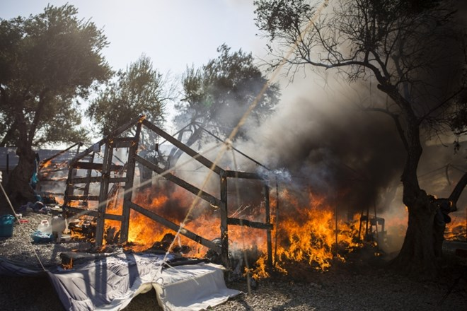 10 September 2020, Greece, Moria: Fire burns through the tents of the already scorched Moria refugee camp that was almost...