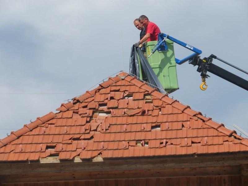 Novinar priloge Moj dom med točo sredi noči na strehi hiše v Črnomlju